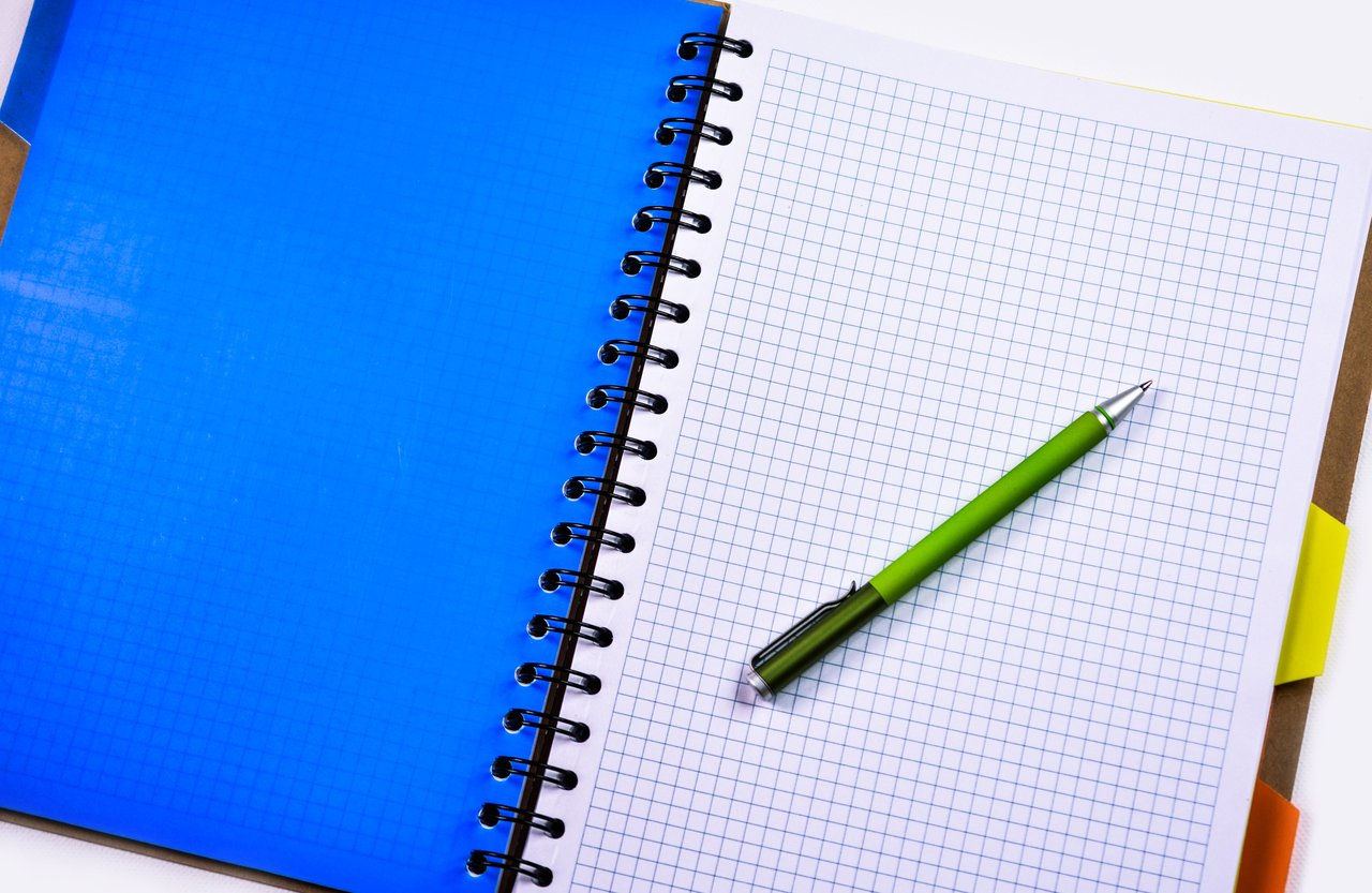 a pen resting on a graph paper notebook